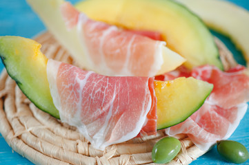 Slices of cantaloupe melon, ham and olives