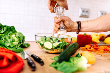Close up details of adding salt and pepper to salad. handsome man preparing salad for healthy life