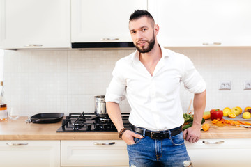 modern lifestyle, man dressed with shirt and jeans cooking and preparing food in kitchen