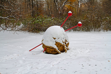 Straw ball of yarn and knitting needles under the snow in the garden