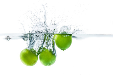 Fresh lime dropped into the water with water splash on a white b