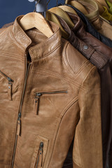 Many colored  leather jacket hanging on rack on blue background