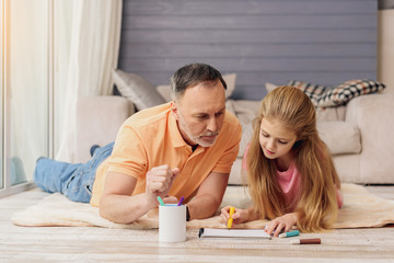 Cheerful old man painting with his granddaughter