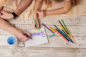 Cheerful grandparent and girl drawing picture together