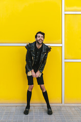 Young man in front of yellow geometric wall