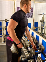 Man in gym workout with fitness equipment. Man holding dumbbell workout at gym. Stand with chrome dumbbells next to mirror.