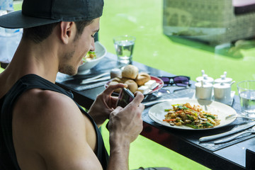 Side view of a handsome young man taking a photo of his food in the restaurant. Horizontal indoors shot.