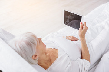 Cool old patient watching at tablet in hospital room