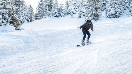 snowboarder rides in motion on the ski slopes