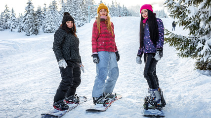 girls snowboarders are on the boards at the ski slopes