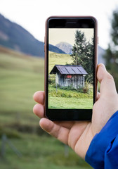 Taking photo of a mountain hut with smartphone