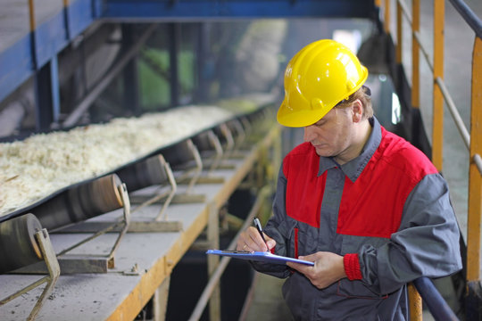 Worker controlling and writing the result of the quality of chopped sugar beet on conveyor belt in sugar refinery