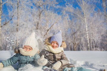 Two little girls smile and play with a snow in a winter