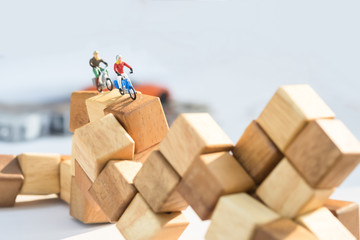 Miniature people riding motorcycle or motor bike on the wooden blocks