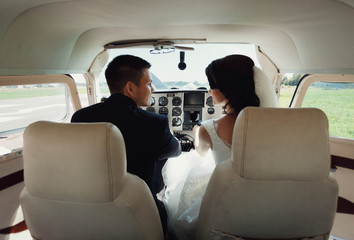 beautiful and young newlyweds sitting in helicopter