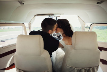 beautiful and young newlyweds kissing in helicopter