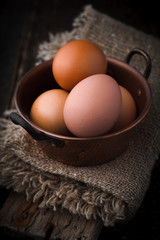 Chicken eggs in the cooper pot on the wooden table vertical
