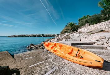 Orange kayak is on the sea pier, Adriatic seaside od Croatia