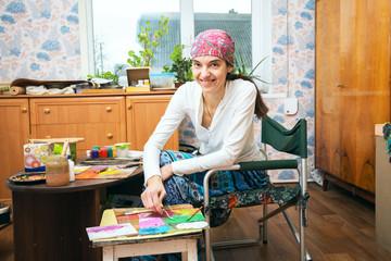 Happy woman artist paints, enjoying  creativity