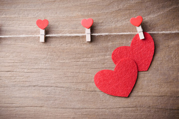 Valentines day concept background.A couple of red heart shape cards hanging on rope with retro wood floor background.