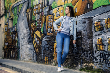 Young and attractive girl is standing next to the graffiti wall and looking somewhere out the camera, Barcelona, Spain