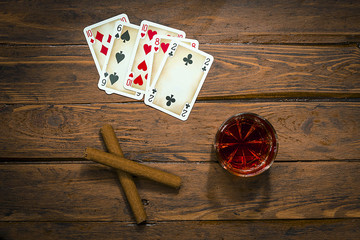 Playing cards, cigar and drink on the old boards