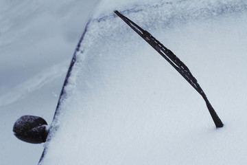 close up of black raised car windscreen wiper covered in snow