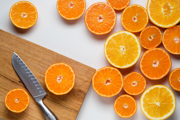 cut oranges and tangerines on a white background