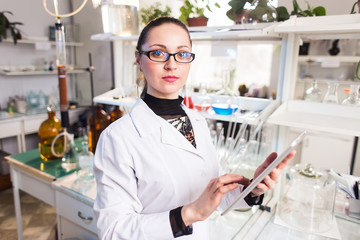 Female scientist in the lab working on the tablet