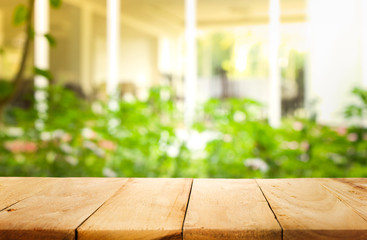 Empty wood table top on blur abstract green from garden in morning