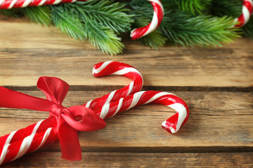 Candy canes with coniferous branches on wooden background