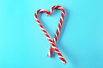 Heart shape made of candy canes on color background