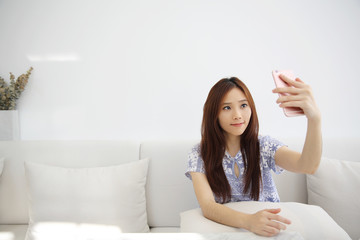 Young beautiful woman photo selfie in white tone