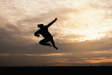 A silhouette of man  jumping in the sunset background.