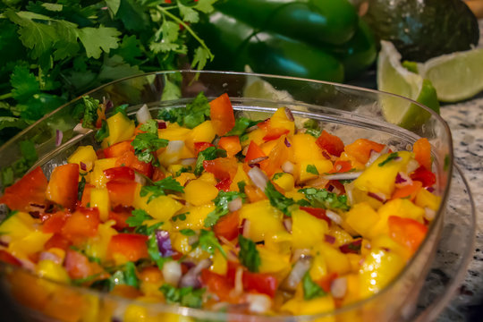 Mango Salsa. Freshly prepared mango salsa in plastic container, in a domestic kitchen with limes and cilantro.