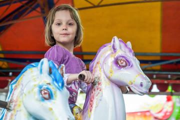 Young girl riding carousel horses