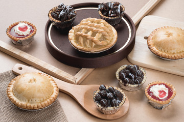 Coconut pie and chocolate mini tart on wooden background