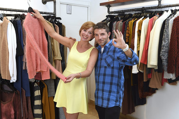 young happy couple shopping together clothes at fashion shop smiling satisfied in love gift