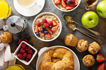 Breakfast table with oatmeal porridge, croissants and muffins
