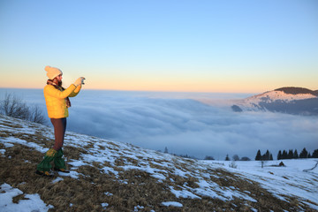 Young woman hiking in winter mountains. Hiker taking photo with smartphone