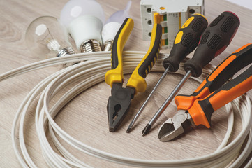 set of electrician tools, a coil of wire and equipment in backgr