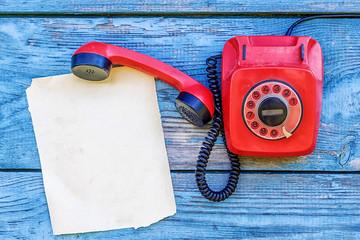 Red retro telephone and a sheet of paper for records