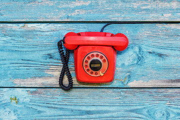 Red retro telephone on the background of old boards