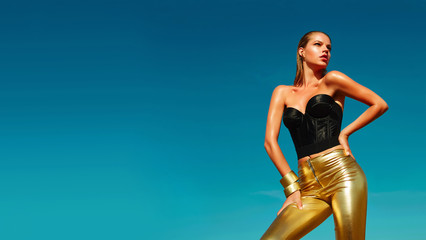 Fashionable girl with a beautiful tan is against the blue clear sky. Girl dressed in a black corset and gold pants. A woman in model pose outdoors. Gold ornaments and bracelets. Promotional poster.