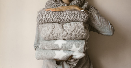 Woman holding a pile of winter wool clothes