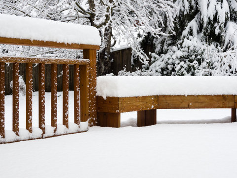 Snow covered wooden deck and backyard