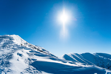 Snowy ridge of mountains, background winter mountains, winter landscape with sun, background european alps, european snowy landscape