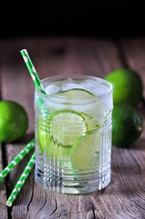 Homemade iced lemonade lime in a crystal glass on the old wooden background.