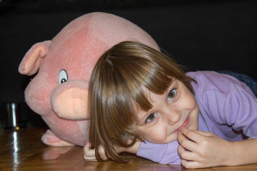 Cute little girl lying on the floor with her stuffed toy pig