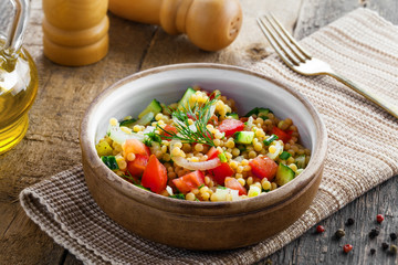 Traditional Israeli healthy meal Ptitim with tomatoes, cucumber and onion for delicious healthy breakfast. Classic Moroccan couscous with vegetables.